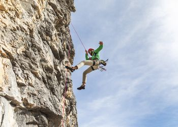 man in a green shirt and red helmet abseiling in the Dolomites mountains