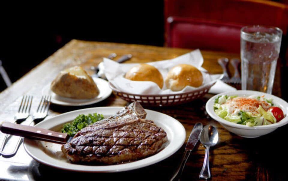 Restaurant dining table with a steak, a bowl of salad, a baked potato, and basket of bread