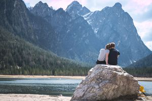A couple sits on a rock cuddling and looking at the view