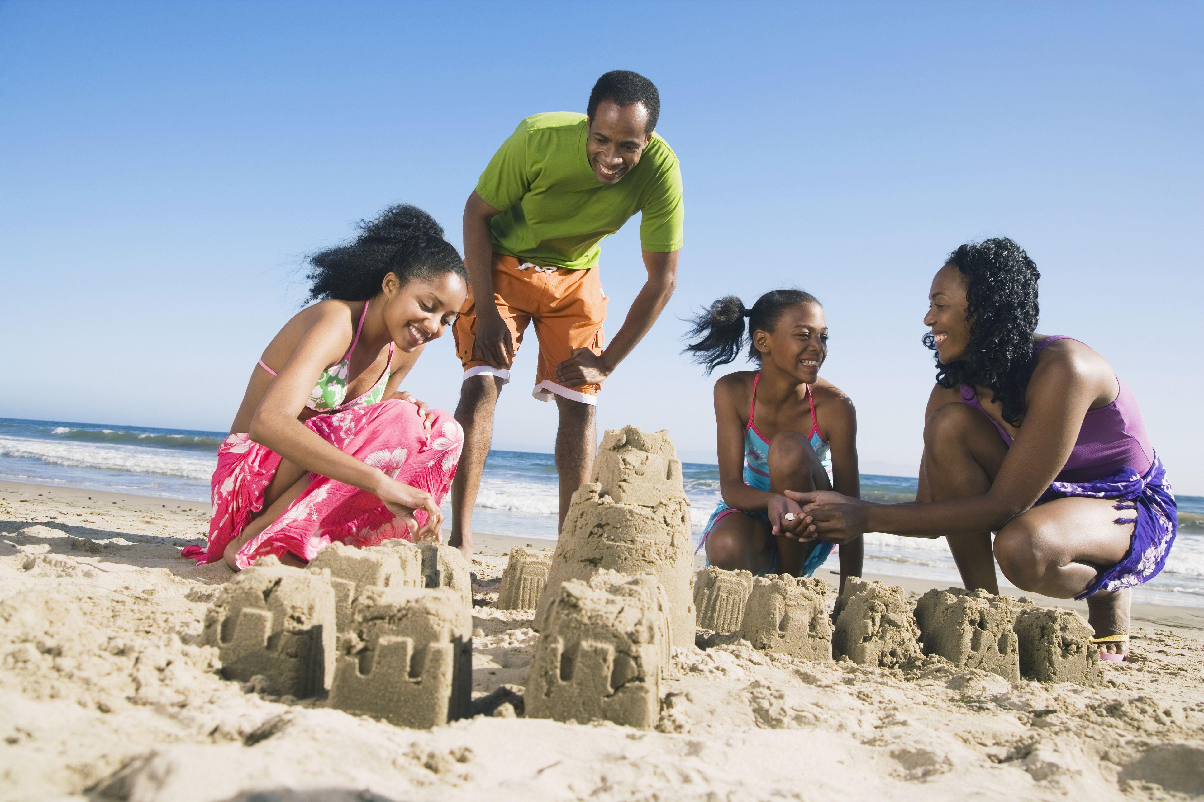 Familia africana construyendo castillos de arena