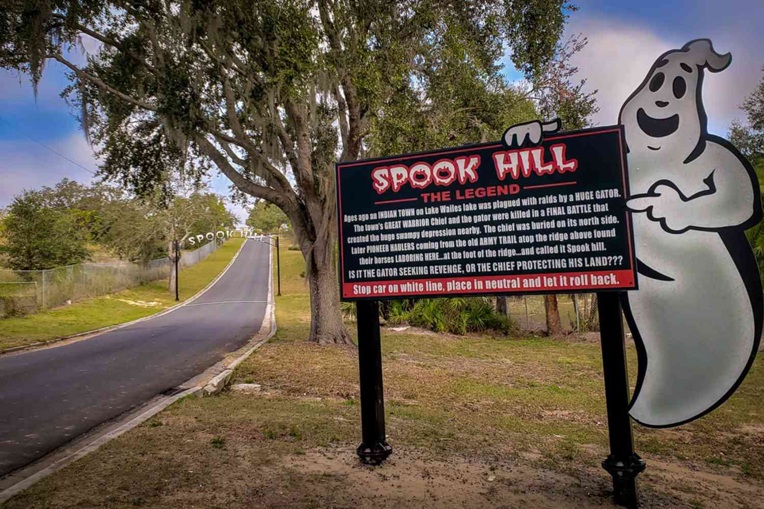 A ghost holding a sign explaining the legend of Spook Hill at the foot of the hill