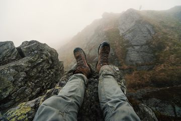 Man sitting on rock with hiking boots on