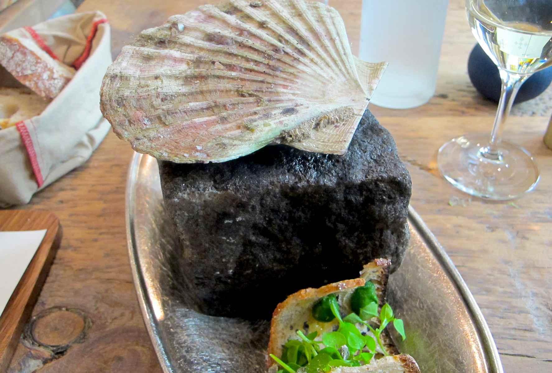 Whole fresh scallop seared on Parisian limestone with toast garnish, at Clover Restaurant