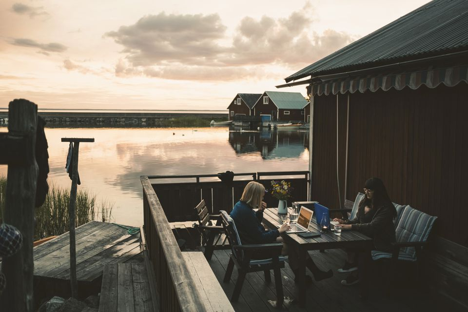 Friends using laptop at table in holiday villa by lake against sky