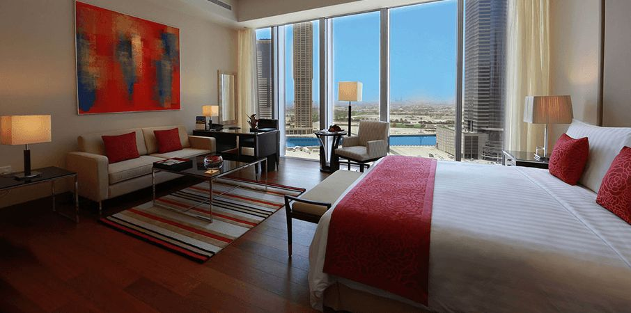 hotel room in the Oberoi Dubai with a bed, couch, table, armchair, and desk