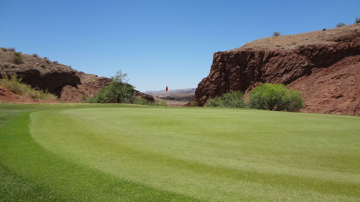 golf green with rock formations on either side