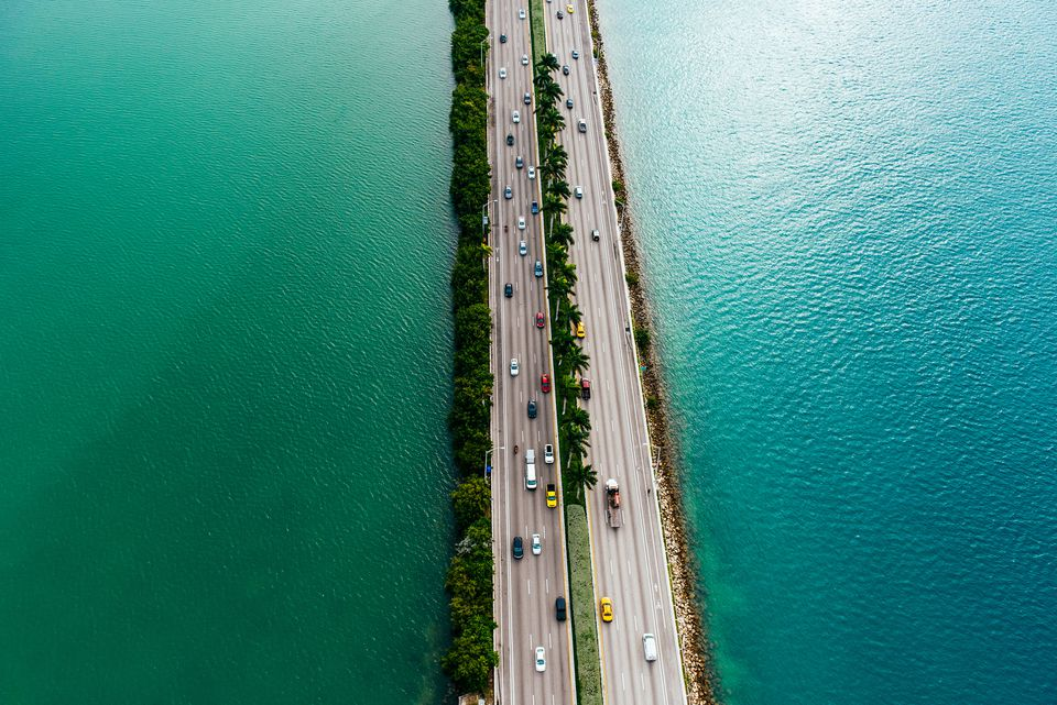 Cars drive on a highway surrounded by the ocean in Miami, Florida