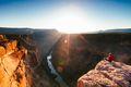 Tourist on the edge of the Grand Canyon at sunrise, USA