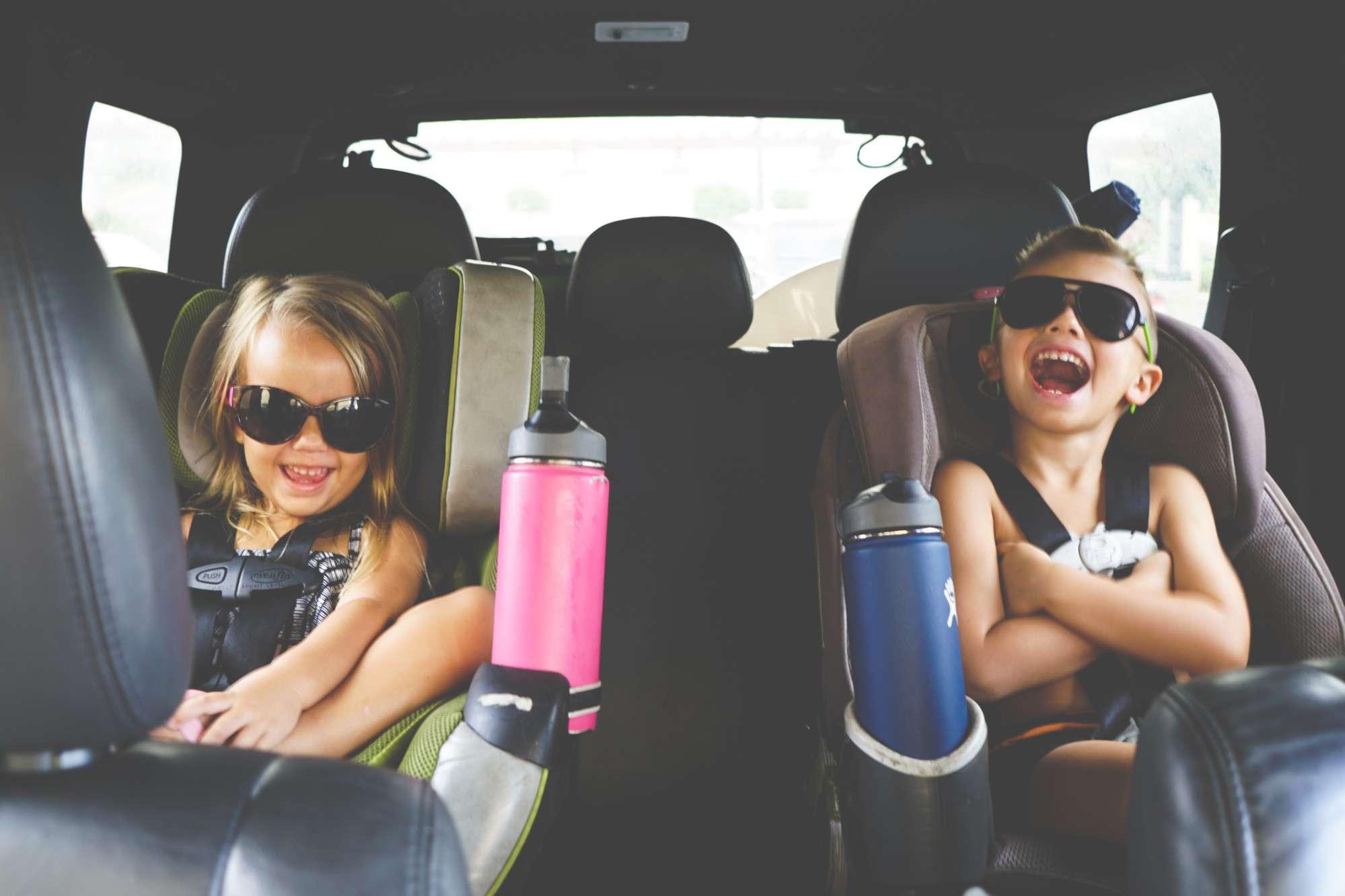 Dos niños en el asiento del automóvil en el asiento trasero con gafas de sol riéndose
