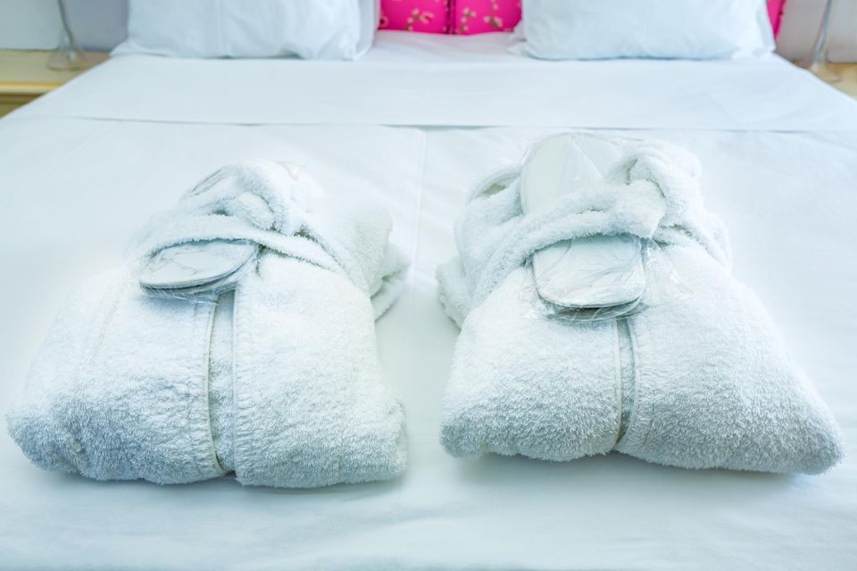 Bathrobes and slippers sitting on the bed at a hotel