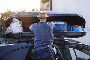 Man loading cargo box on his car