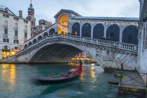 Rialto bridge with passing gondola. Venice, Italy.