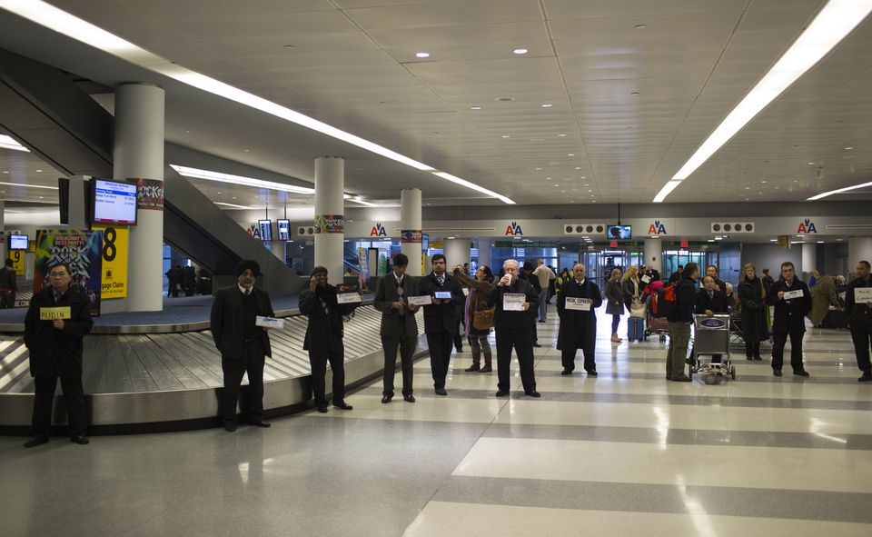 A group of private limousine drivers wait for arriving passengers at JFK International Airport