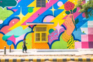 Woman walking by a colorful street mural in Lodhi Colony