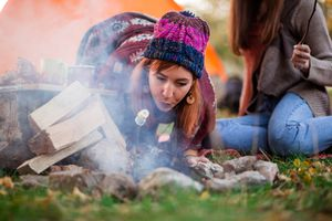 Redhead Girl Starting Campfire By Orange Tent