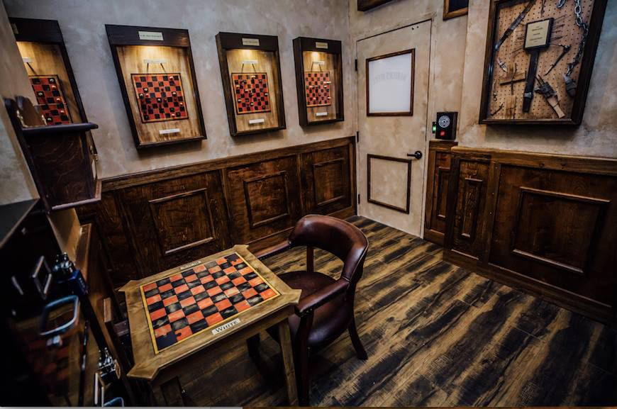 Prison Break escape room at The Escape Game with framed checkerboards on thewas and a checkerboard table with one chair