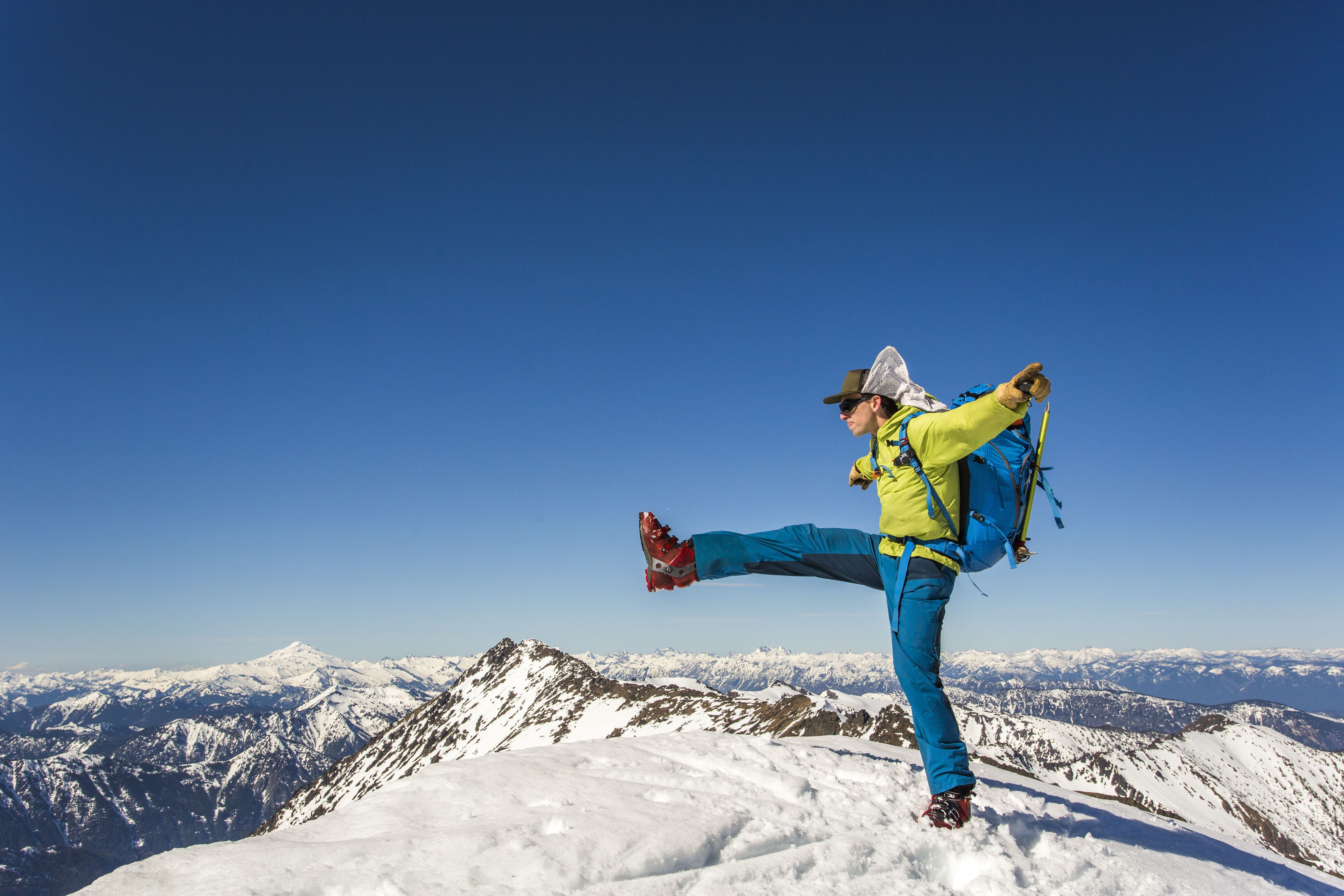 Backpacker standing on one leg on top of snowy summit against clear blue sky, Leavenworth, Washington, USA