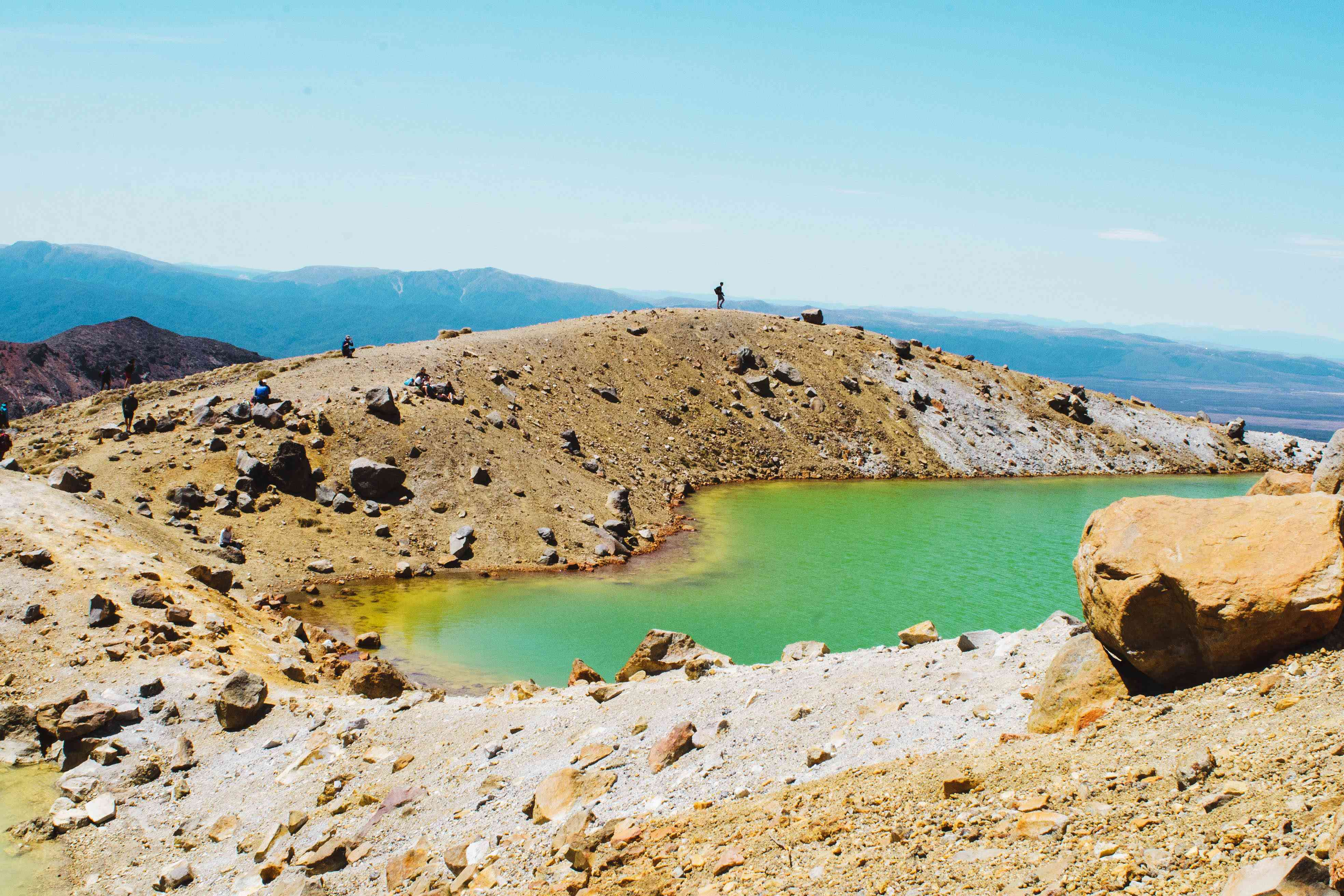 Una persona que camina sobre una gran colina junto a una piscina de agua de color gema
