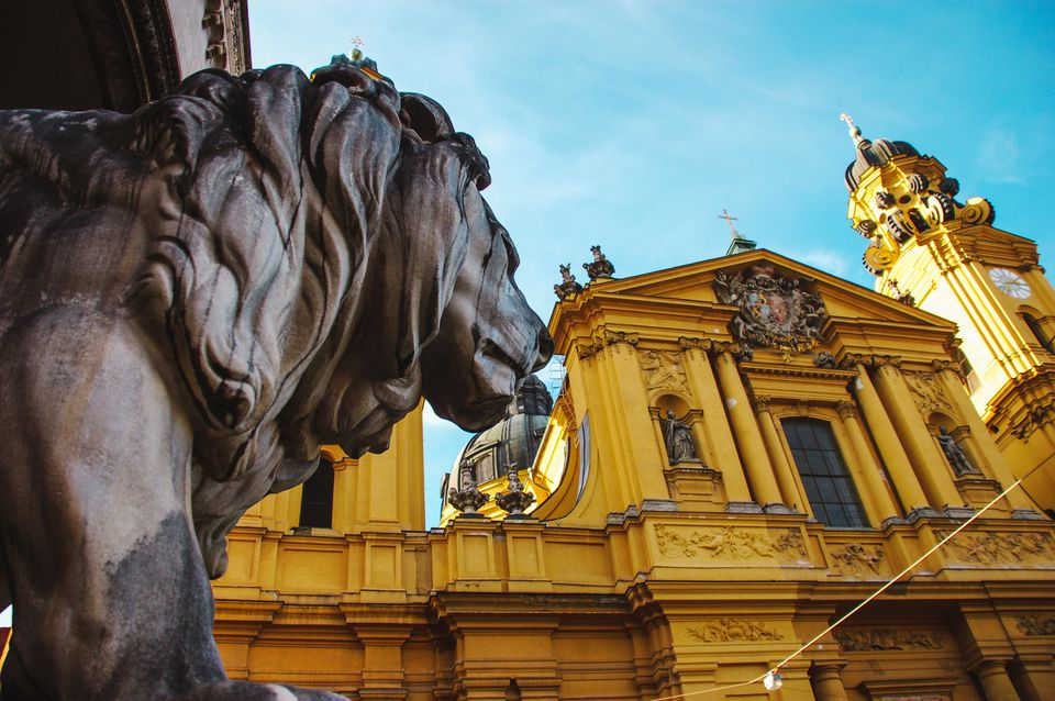 a lion statue looking at a yellow building in Munich