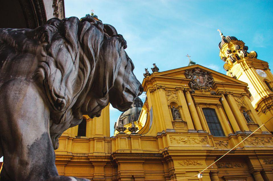 ¿Una estatua de león mirando un edificio amarillo en Munich