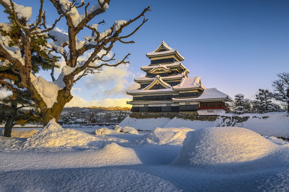 Matsumoto Castle (Crow Castle) covered under snow in winter from red bridge, Japan