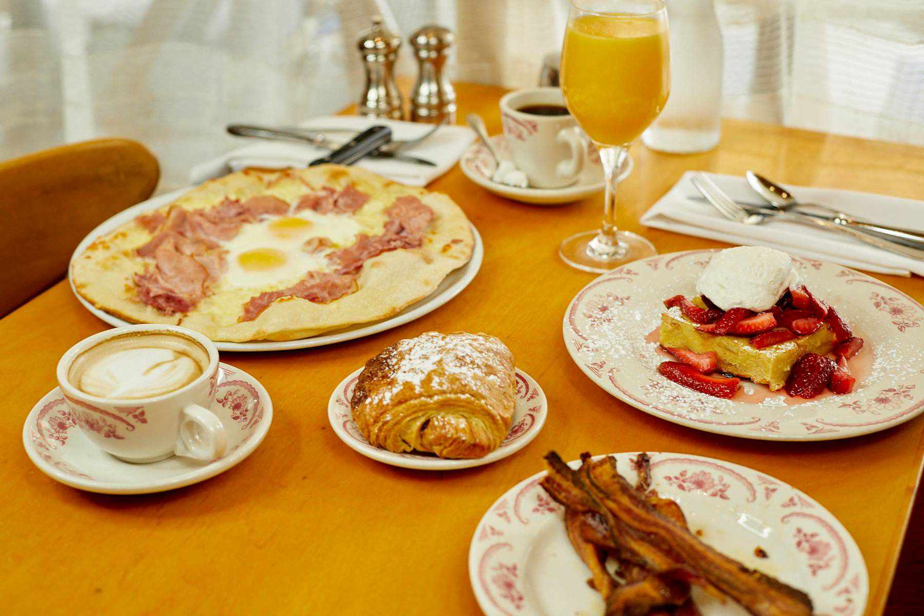 French toast with strawberries and whipped cream, a side of bacon, a croissant, a flatbread with two sunny-side-up eggs and ham, a latte, a cup of coffee, and a wine glass filled with orange juice on a table at Rose's cafe in san francisco
