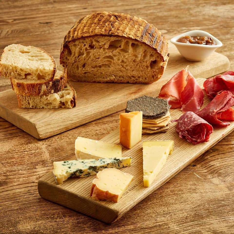 two narrow wooden boards, one with pieces of bread, the other with cured meats, crackers, and pieces of cheese