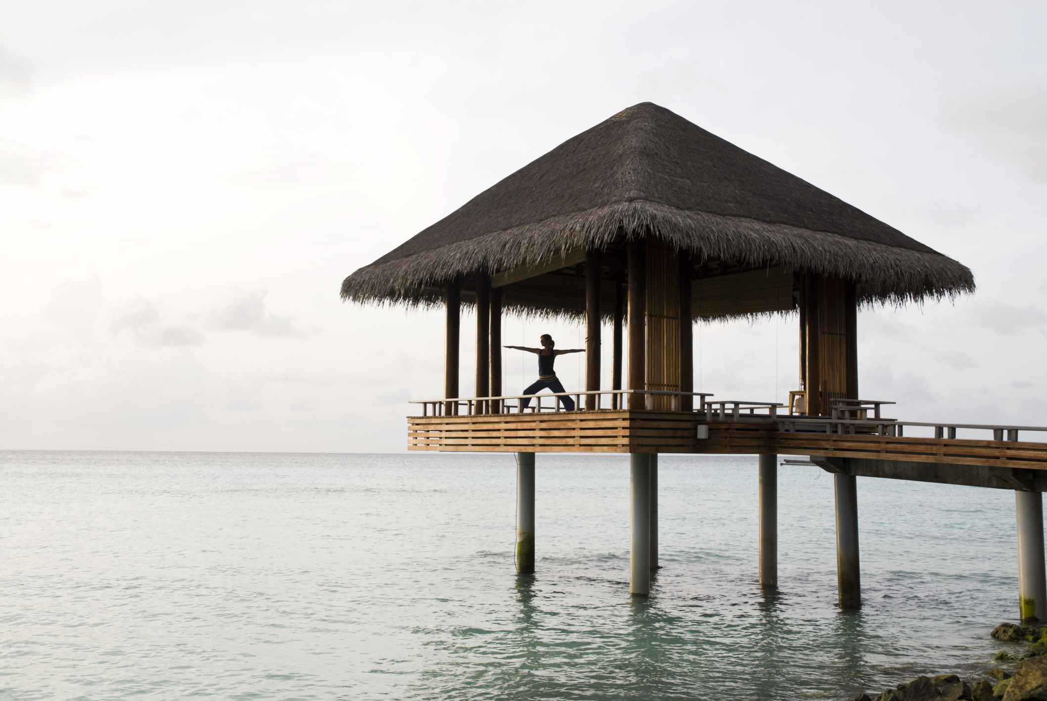A woman practicing yoga poses on an open air, over water platform at a luxury resort in the Maldives.