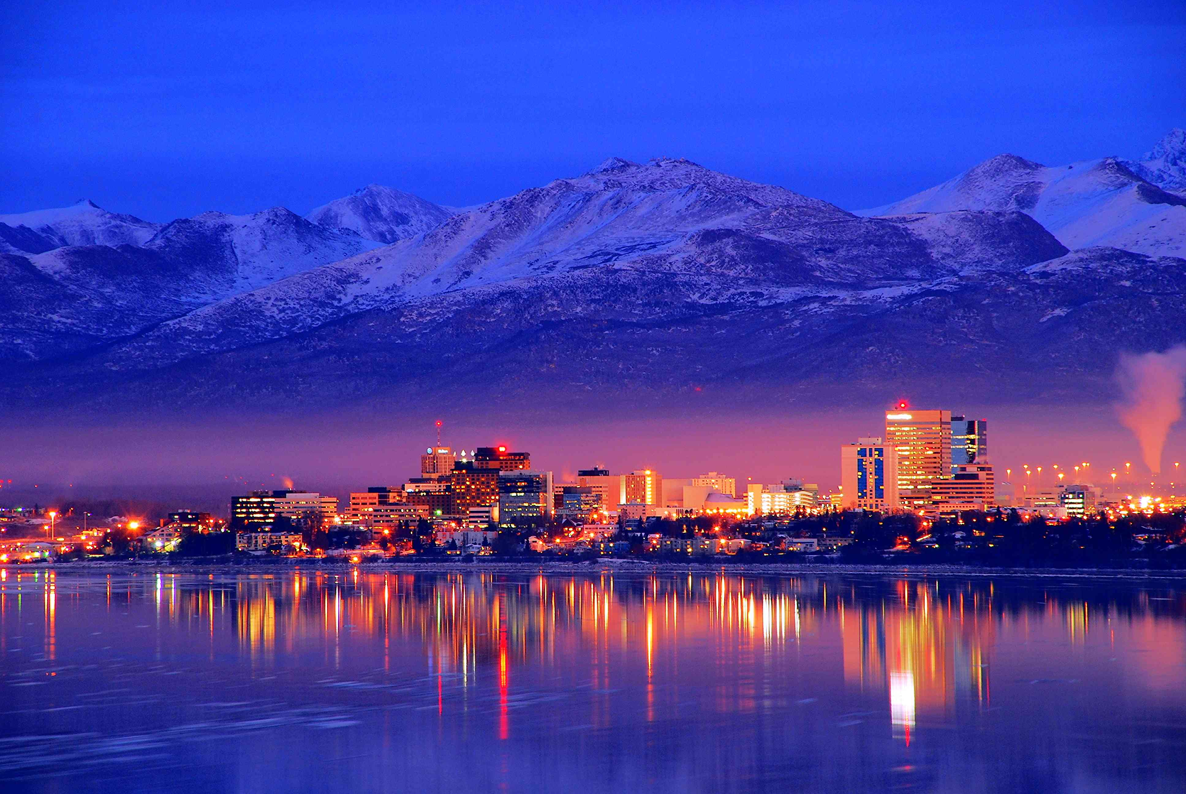 city skyline at night with water reflecting orange lights and mountains in the backgroud