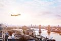 airplane in the sky over Tower Bridge in central london