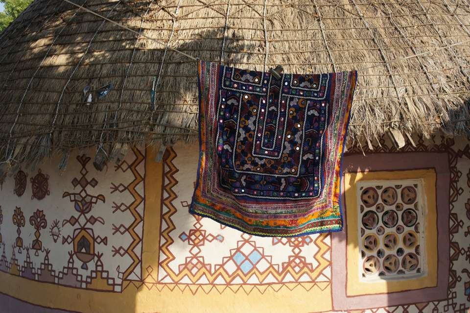 Embroidered cloth hanging from a clothesline infront of a decorate straw-roofed house