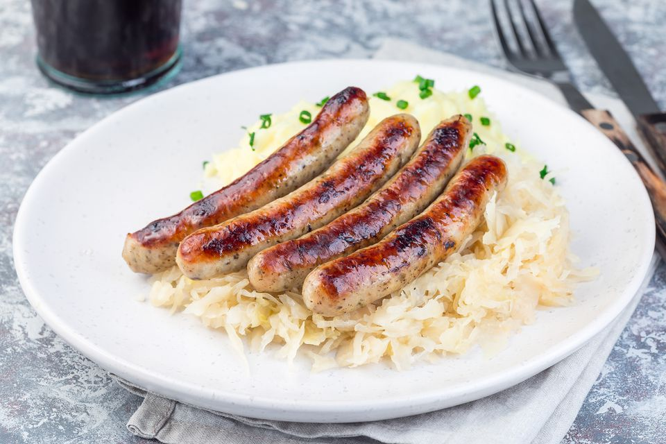 Roasted nuremberg sausages served with sour cabbage and mashed potatoes, horizontal