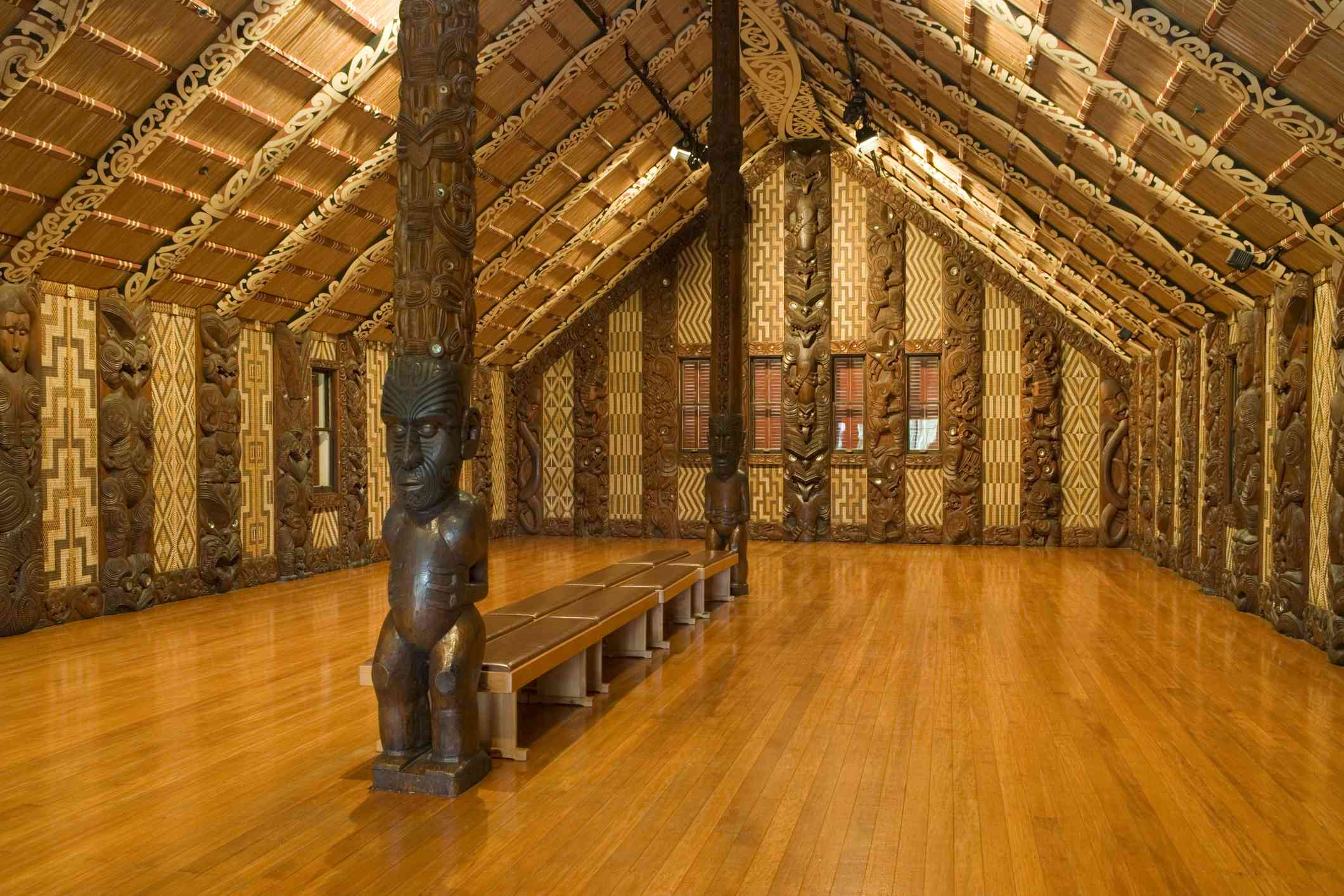 Maori carvings inside a building with polished wooden floors