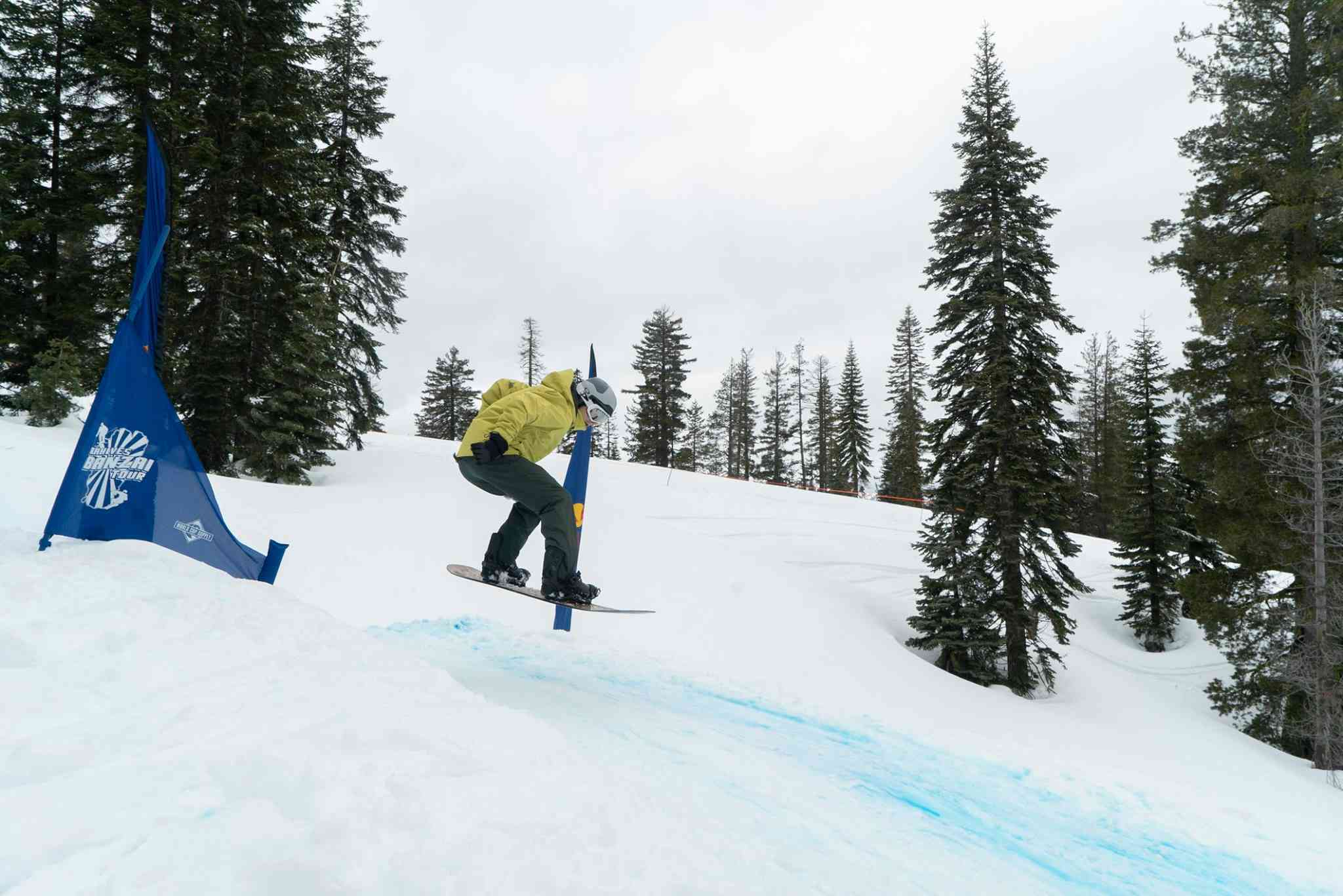 Snowboarder jumping down a slope with two blue flags on either side of them