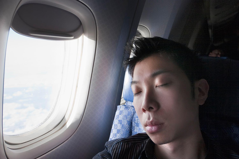 Hombre durmiendo en un avión