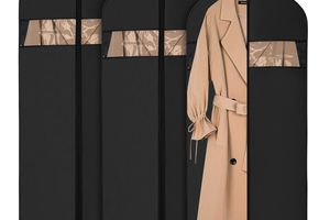 tan trenchcoat in garment bag with two others behind it on white background