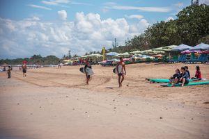 Surfers walking down Kuta beach