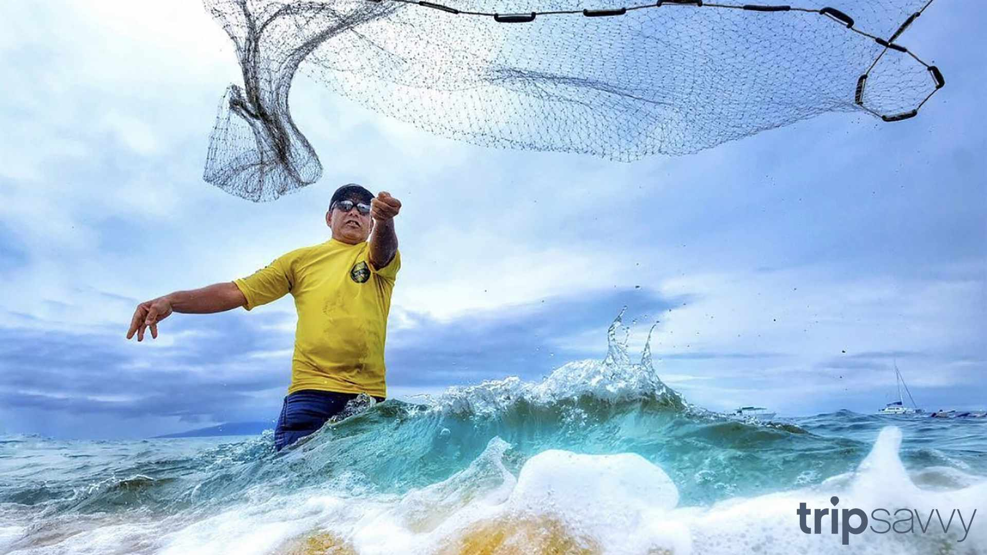 A man throwing a fishing net in the waters of Maui