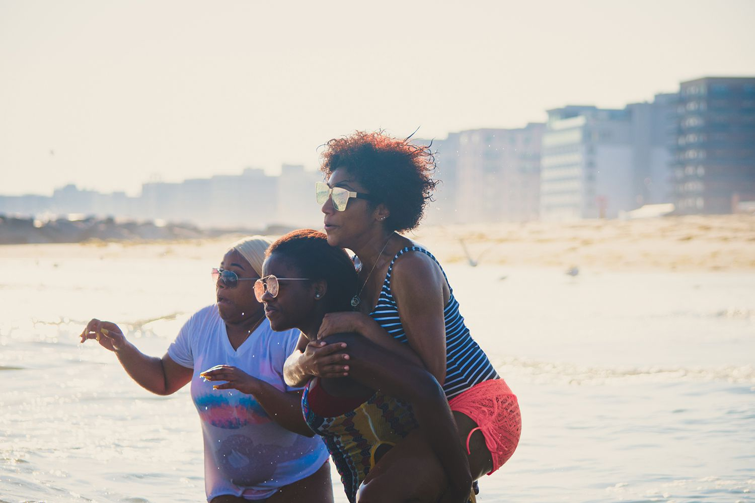 Three beautiful young black female friends playing in the water at the beach on a hot summer day.