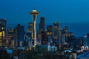 The sun sets on the Space Needle and downtown skyline at dusk