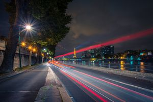 Street view of Paris highway along the river with the Eiffel tower in the distance