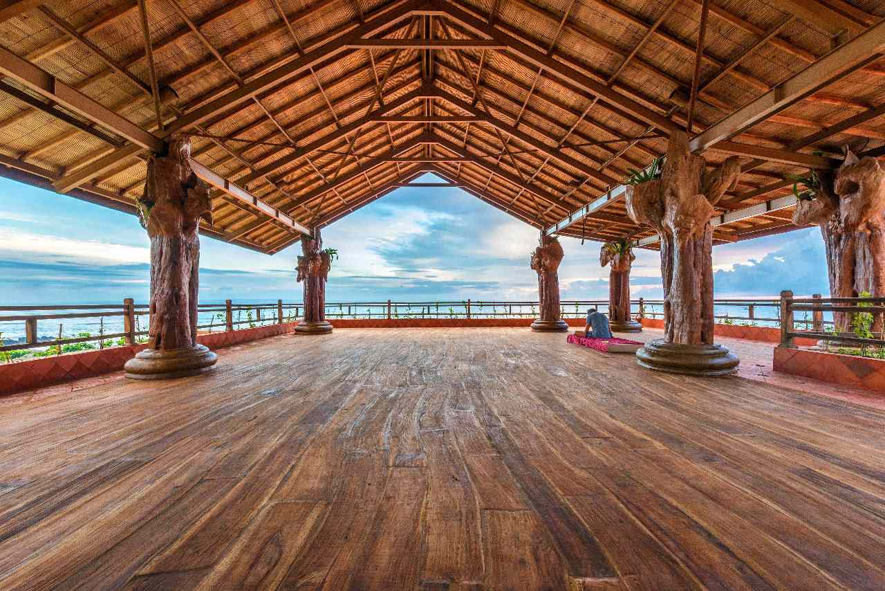 Empty covered, outdoor yofa studio in Bali. The floor is woonden and there are wooden posts supporting the roof
