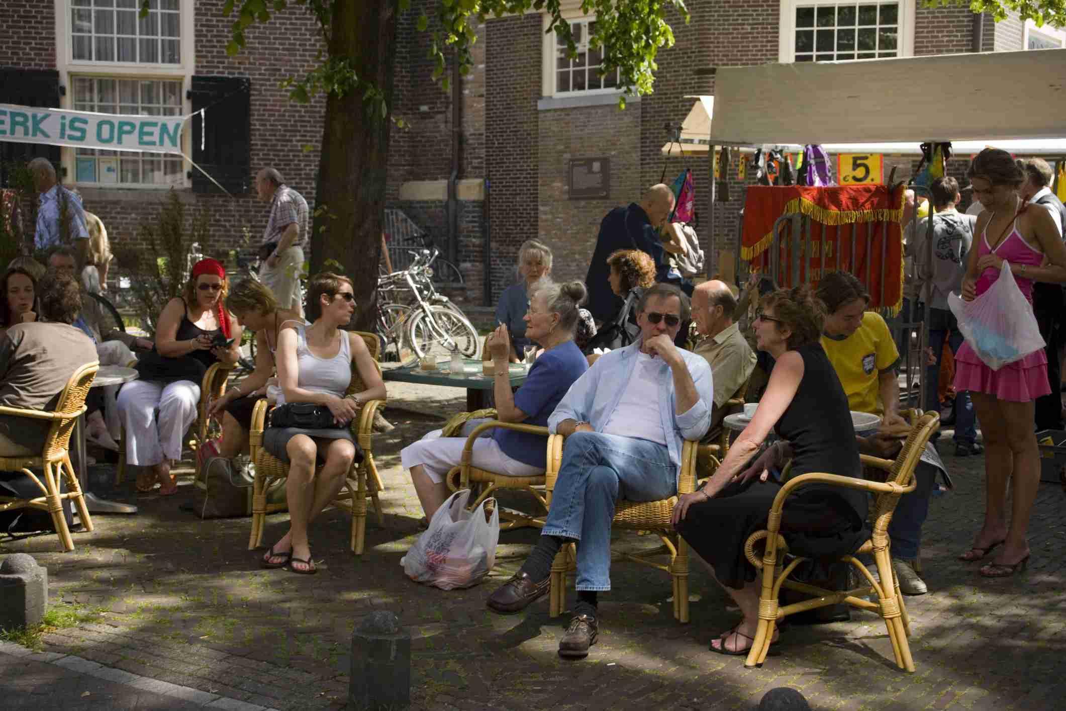 People sitting in open air cafe, monday flea market Noordermarkt,