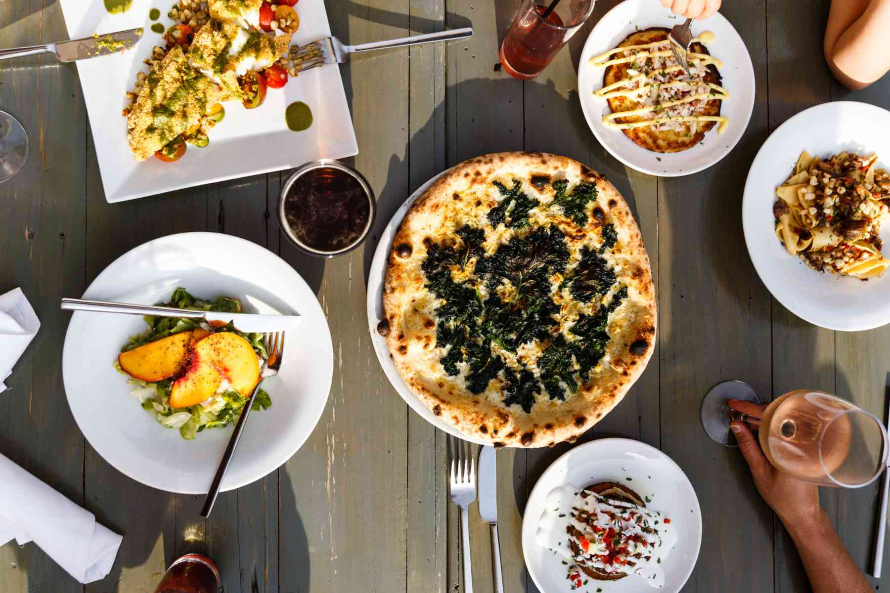overhead shot of a wooden table with an assortment entree with a spinach pizza in the center