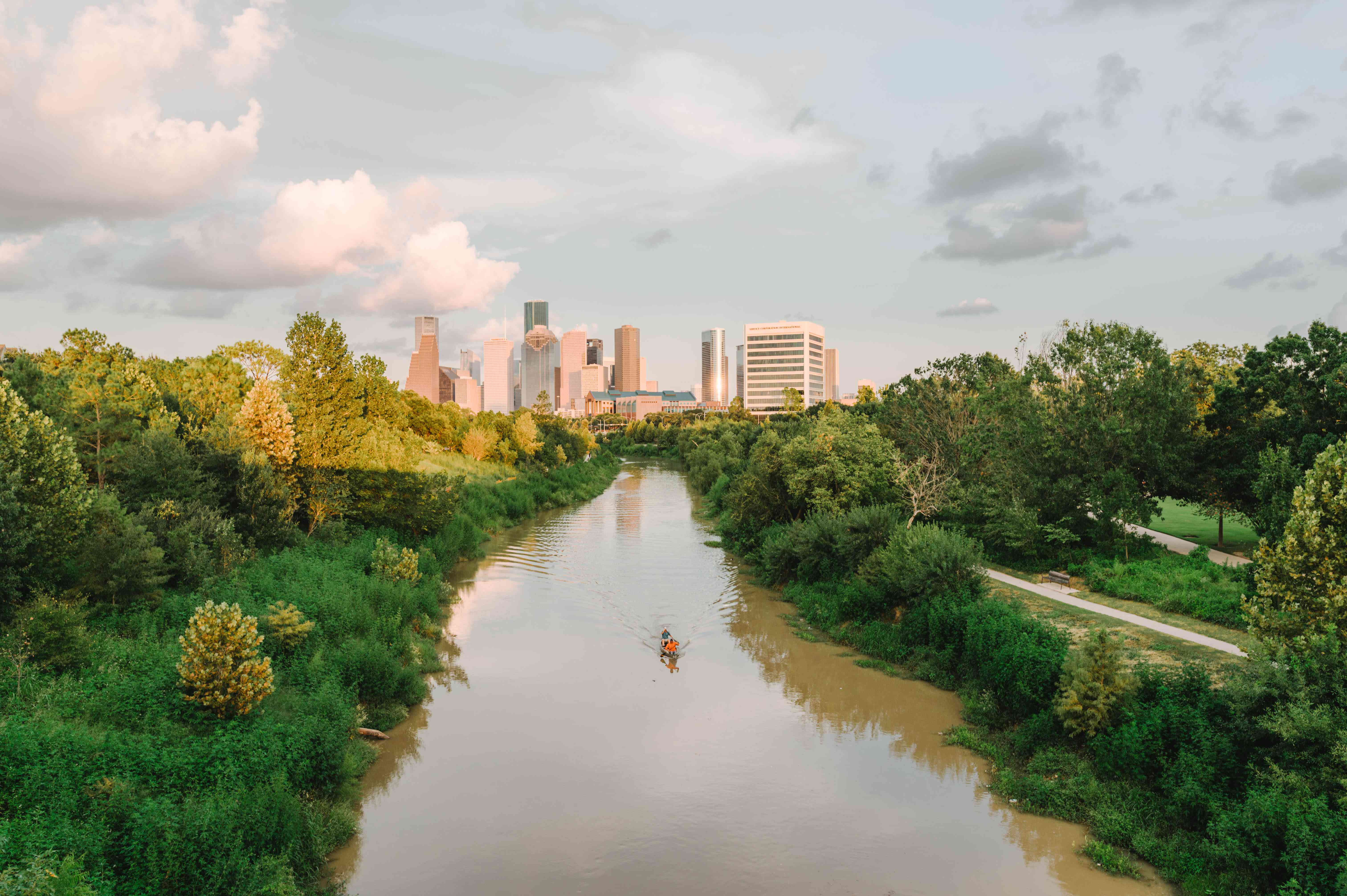 Someone kayaking down the river in Buffalo Bayou with the Houston skyline in the background