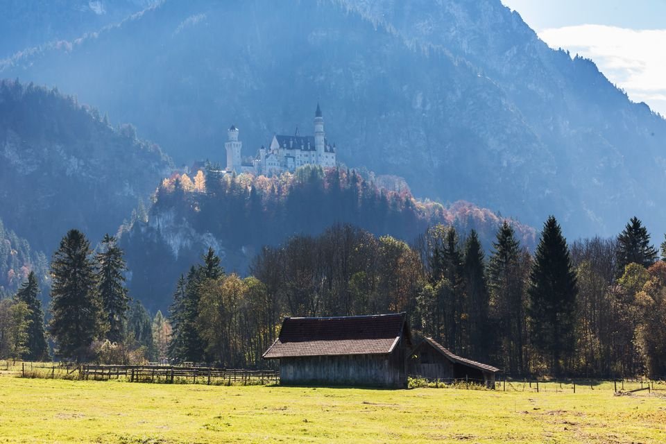 Neuschwanstein castle with alps and a hut in the foreground