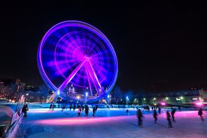 People enjoying the ice rink in front of Montreal's giant ferris wheel, Canada