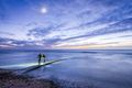 Night at beach, two night divers on the trestle road