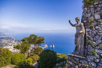 Statue of Tiberius in Capri island with a view of Faraglioni rocks, Italy