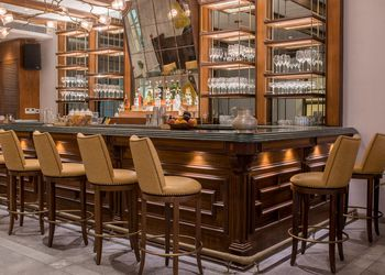 Chairs around a wooden bar at a restuarant